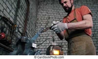 Blacksmith in forge makes steel knife, small business