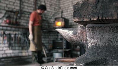 De-focused up view - hands of Blacksmith with gloves in...