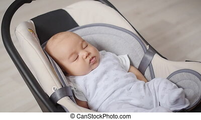 The kid lies in the chair - The kid lies in the safety seat