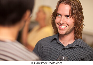 Smiling Young Man with Glass of Wine Socializing in a Party...