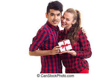Young couple holding a present - Young smiling man with...