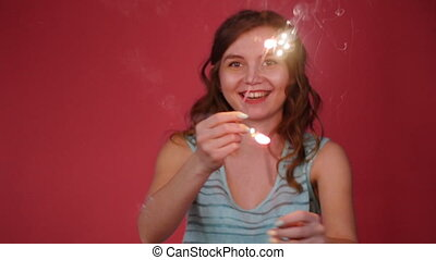 Beautiful smiling woman dancing with a sparkler