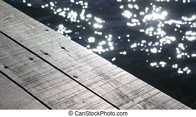 Wooden pier. Half of the frame is a tree, the second half is...