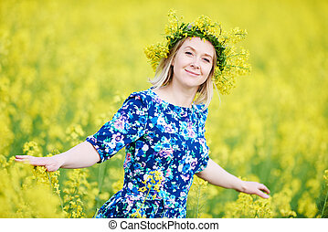 woman with flower garland at yellow rape seed meadow