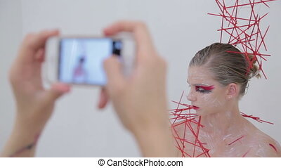 4 shots. Make up artist taking photo of her client with...