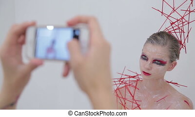 Make up artist taking photo of her client with creative...