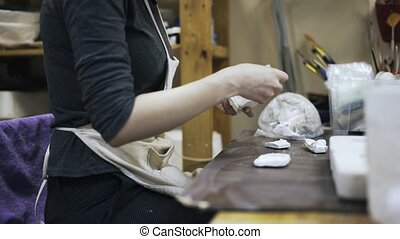 Woman s hands putting pieces of gypsum, pan shot - Side view...