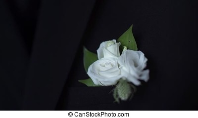 White flower in his jacket pocket closeup. Groom boutonniere...