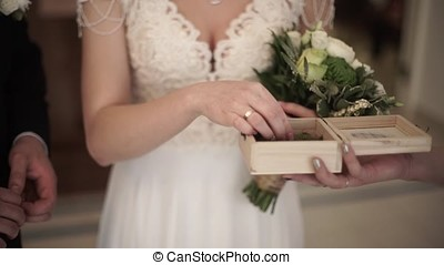 Closeup of a bride putting a gold wedding ring onto the groom's finger. wedding rings and hands of bride and groom. young wedding couple at ceremony. bride wear ring on groom's finger.