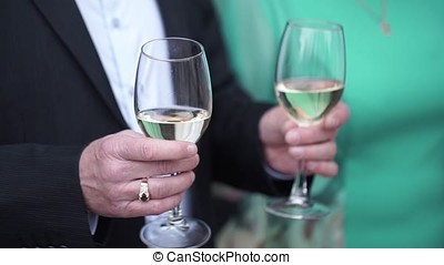 Close up of Caucasian man in black suit and white shirt holding two tall glasses with white wine. Closeup of two glasses of champagne on tray holded by handsome waiter in tuxedo. Man in suit holding 2 glasses