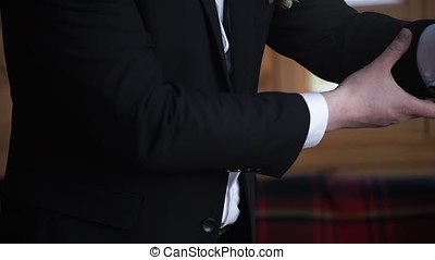 Man buttoning on a black jacket. Wedding details - elegant groom dressed wedding tuxedo costume is waiting for the bride. businessman buttoning jacket, getting dressed. Groom buttons jacket