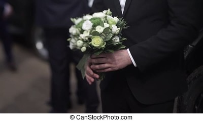 Handsome businessman holding flowers. Groom in a suit holding a bouquet of flowers. Wedding boutonniere. Elegant man dressed in a modern black suit and white shirt holding in hand a wedding flowers. Closeup