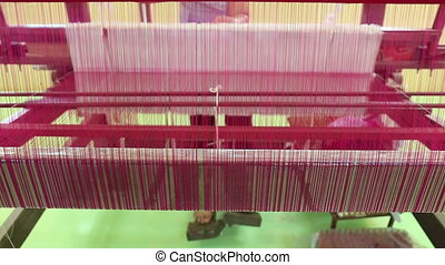 weaving brocade using a traditional loom machine with yarn