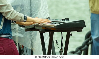 Musician plays a synthesizer, shooting side of the river...