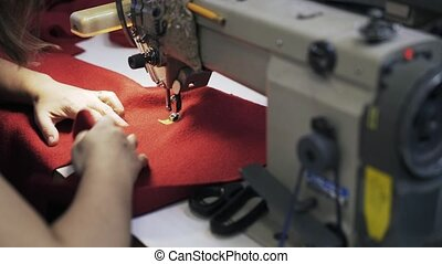 Close up of woman s hands sewing red fabric