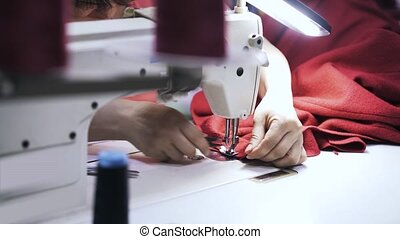 Woman cutting thread and sewing two pieces of red fabric