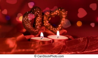 Valentines day, two candles burning in front of hearts, closeup