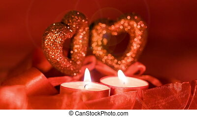Valentines day, two candles burning in front of falling hearts, closeup