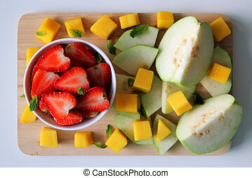 Fresh fruits – guava, mango and strawberry with leaves of mint on the white background.