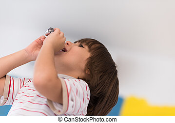 kid blowing a noisemaker - young happy boy having fun and...