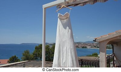 The bride's dress flutters in the wind on the balcony, against t