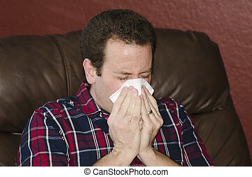 Seasonal allergies got you down? Man blowing his nose while...