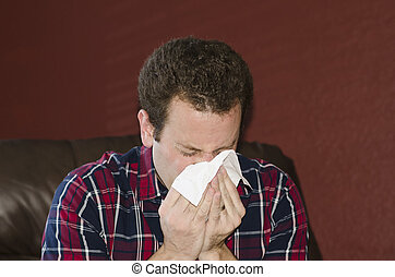 Sick man blowing his nose into a tissue. - Sick man at home...