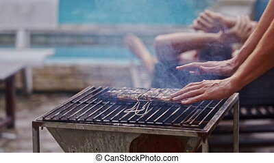 Guy Controls and Turns Frying Meat on Barbeque Grill