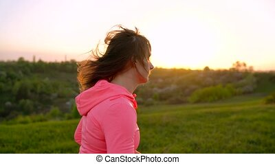 Woman runs outdoors at sunset, slow motion - Young woman...