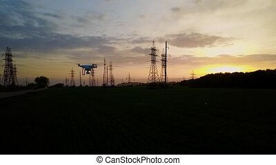 Drone flies over power lines at sunset - Aerial syrvey -...