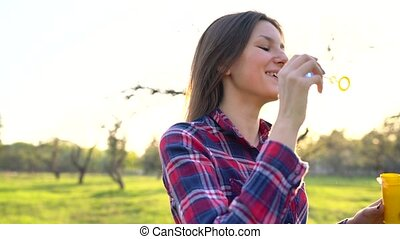 Woman blowing soap bubbles outdoors - Happy woman blowing...