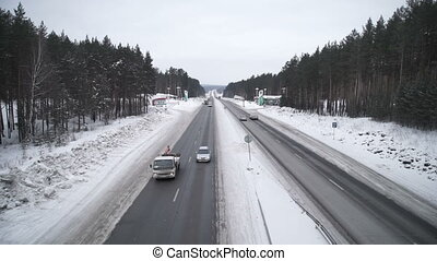 the road in the winter. Cars driving on the road
