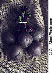 Bunch of beetroot on a brown burlap cloth in artistic conversion