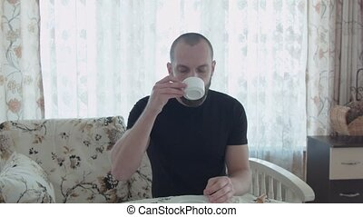 A young handsome man is drinking coffee for breakfast. He gets up, goes to the window, opens it.