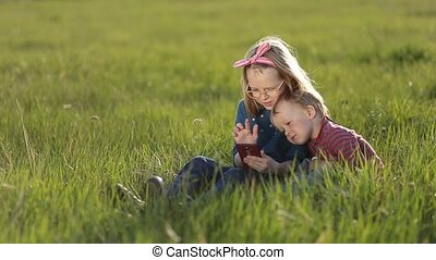 Cute kids playing on smartphones sitting on grass.