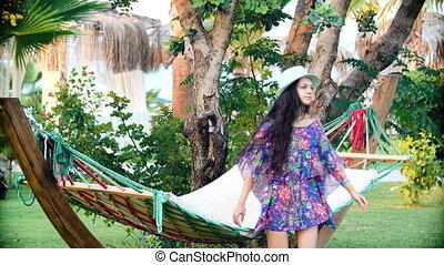 young brunette woman in hat relaxed in hammock on tropical...