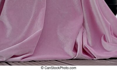 Pink velvet fabric fluttering in the wind. Close. Table...