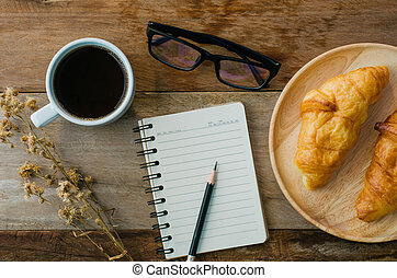 Croissants coffee notebook eyeglasses pencil on the wooden table - tone vintage
