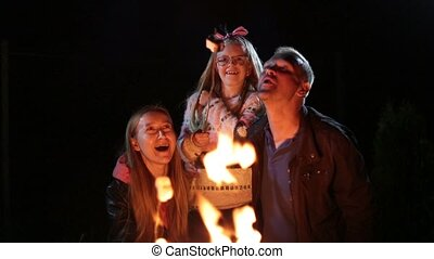 Happy family roasting marshmallow over campfire - Cheerful...