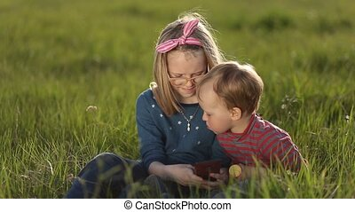 Smiling siblings relaxing on green grass in spring