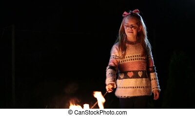 Sweet girl overroasting marshmallow over campfire - Sweet...