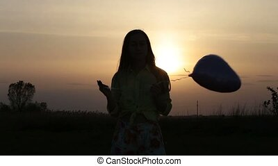 Pretty woman with heart shaped balloon at sunset -...