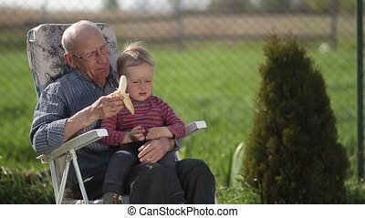 Grandfather giving banana to his grandson outdoor.