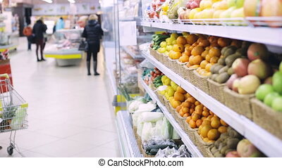 woman with food in shopping cart at grocery store