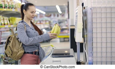 woman weighing food on scale at grocery store - woman...