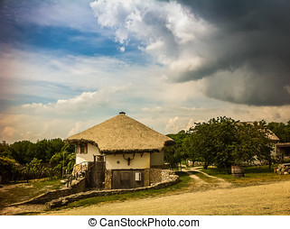 Village house and approaching storm, summer russia