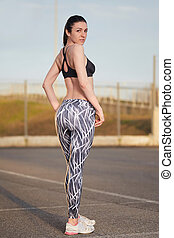 young female runner with perfect figure dressed in sport bra...