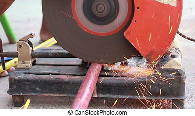 Worker in gloves cutting a metal pipe pieces with angle grinder at outdoor