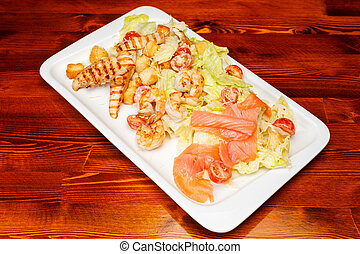 salad of romaine lettuce with prawns, smocked salmon, croutons, grilled chicken, cherry tomatoes with caesar dressing and grated parmesan