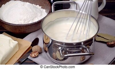 bechamel sauce in a pan and ingredients - Preparation of...